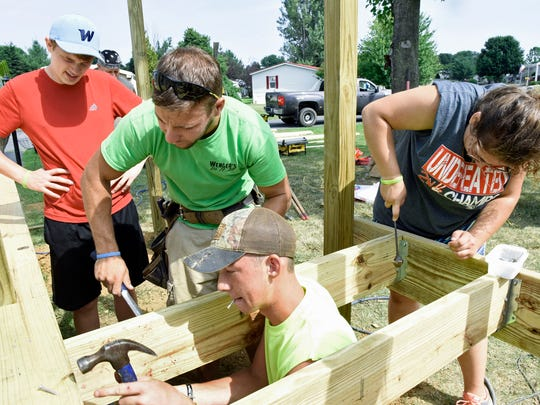 Josiah Wenger, second from left, works with students in the Chambersburg Project on Tuesday, July 12, 2016 at a mobile home in Shippensburg. From left, Tyler Baker, (Wenger), Luke Ritz and Shelby Denlinger build anew porch.