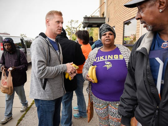 Brian Leitza hands out fruit and sandwiches Saturday,
