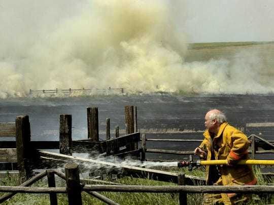 Former Black Eagle Volunteer Fire Department Chief, Tom Martin works to keep a field fire from spreading to structures north of Great Falls on June 29, 2006.