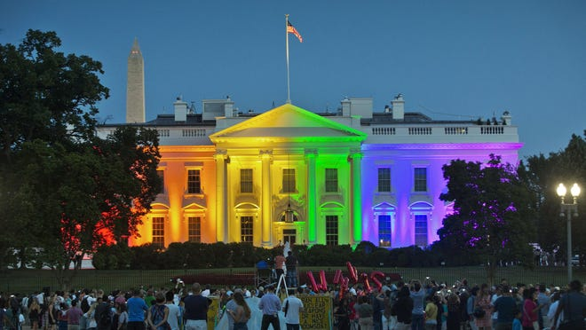 FILE - In this Friday, June 26, 2015 file photo, people gather in Lafayette Park to see the White House illuminated with rainbow colors in commemoration of the Supreme Court's ruling to legalize same-sex marriage in Washington. The Trump administration Friday, June 12, 2020, finalized a regulation that overturns Obama-era protections for transgender people against sex discrimination in health care.