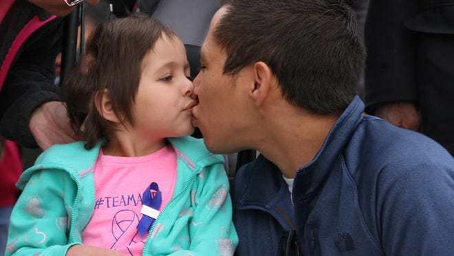 Audi Santistevan and her father, Bo, share a kiss before the start of Friday's Day of the Young Child March in Deming. The march drew attention to National Child Abuse Awareness and Prevention Month.