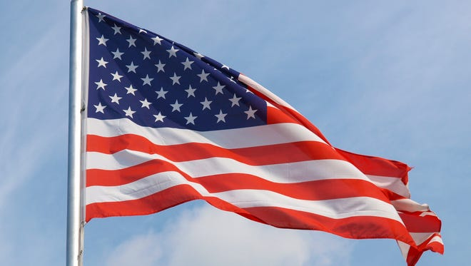 The national flag of the United States of America over a blue sky.