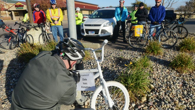 Chris Parsley, president of Falls Area Bicyclists affixes a sign to a ghost bike in memory of Dale Kimpton who was hit while riding last week along 41st Street and later died of his injuries, Oct 17, 2015.
