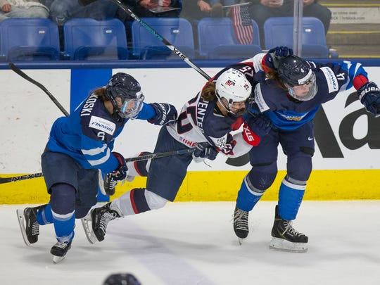 Finland's Jenni Hiirikoski (6) and Rosa Lindstedt (4) put a check on Team USA's Alex Carpenter during Monday's game.