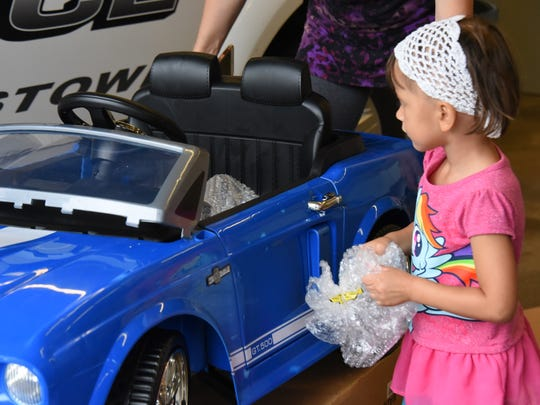 Kaylynn, of Hackettstown, who had her Power Wheels Mustang stolen on July 10, inspects her new model.