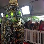 Josh Henderson signs 9 liter G.H. Mumm bottle covered in celebrity signatures at Kentucky Derby