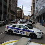 Police vehicles block a road near Parliament on Wednesday, Oct. 22, 2014, in Ottawa, Ontario. Heavily-armed Canadian police backed by armored vehicles surrounded Parliament after at least one gunman shot a soldier guarding a nearby monument and entered Parliament.