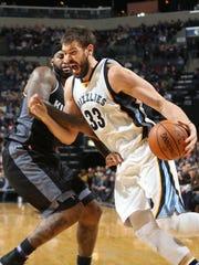 Memphis Grizzlies center Marc Gasol drives to the basket, defended by Sacramento Kings DeMarcus Cousins, left.