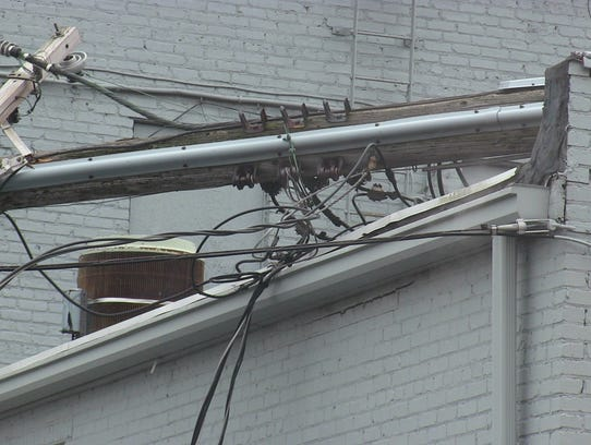 A collapsed utility pole sits on the roof of LynnIvan