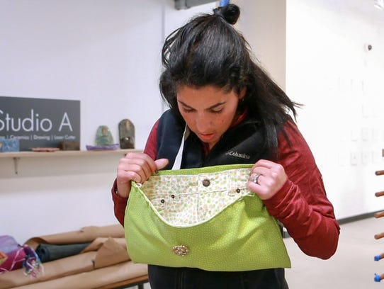 Elyse Weinbaum looks inside the purse she made at the