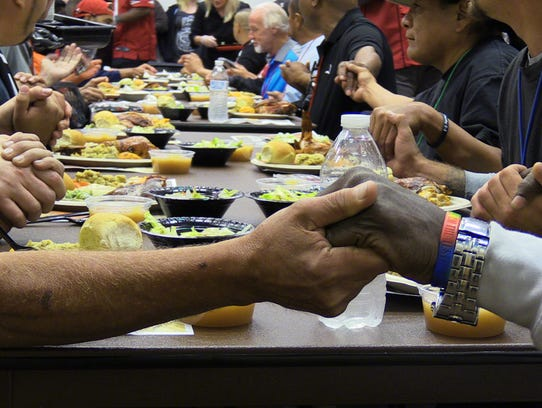 Patrons of the Phoenix Rescue Mission say grace before