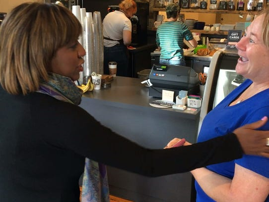 Yvette Simpson talks to a person in CooKoo Coffee in