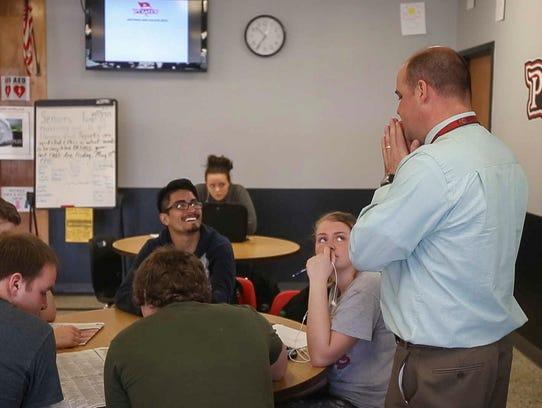 Postville principal Brendan Knutson talks with students