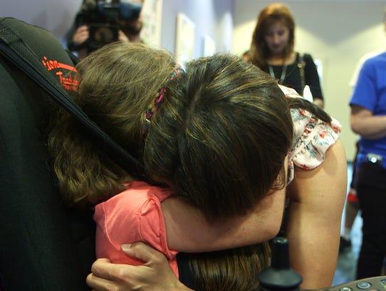 Emily Pederson hugs her daughter Klara after she receives