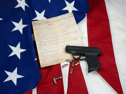 Constitution with Hand Gun and Cartridges on American Flag