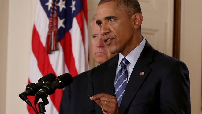 """President Barack Obama, standing with Vice President Joe Biden, delivers remarks in the East Room of the White House in Washington, Tuesday after an Iran nuclear deal is reached. Obama heralded a historic nuclear agreement with Iran Tuesday as an opportunity for the longtime foes to move in a """"new direction,"""" while sharply warning Congress that it would be irresponsible to block the accord."""