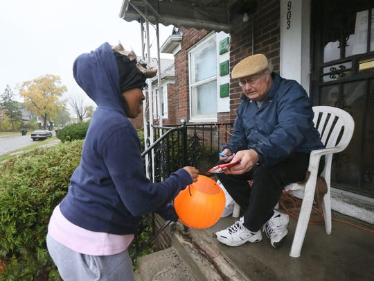 On Halloween in 2013, Zanaija McIntrye, 11, of Detroit goes trick or treating on Alma st. in Detroit and gets candy from Nick DiNunzio. DiNunzio coordinated with 20 of his neighbors to make sure Halloween is enjoyable for the kids.