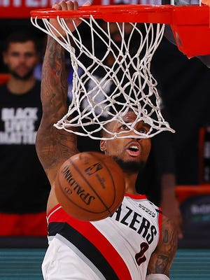 Damian Lillard dunks  against Philadelphia during the fourth quarter on Sunday.