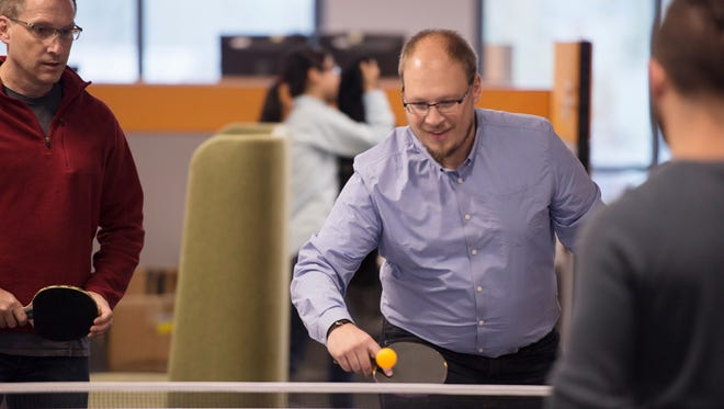 Vess Bakalov plays table tennis with employees at SevOne's headquarters in Wilmington, Del.