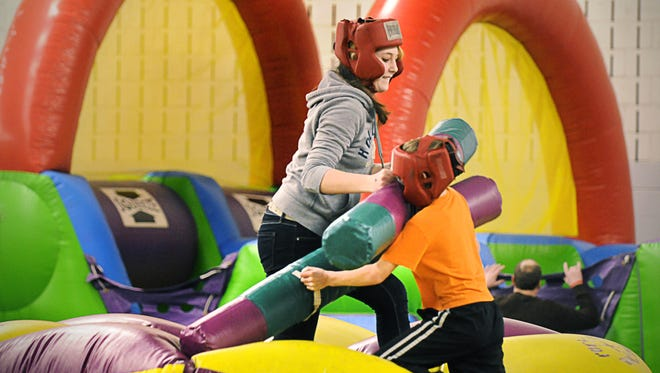 Cassie Cotten of Sartell and her brother Nathan go at it in the Rock 'em Sock 'em game in 2012 during the New Year's Eve Family Fun Fest at St. Cloud State University.