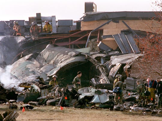 Members of the military and fire departments look through the wreckage after a C-130 military cargo plane crashed into the Drury Inn and JoJo's restaurant February 6, 1992. The crash killed the plane's crew of five and 11 people on the ground. Part of the fuselage of the plane is visible here at the rear of the restaurant.