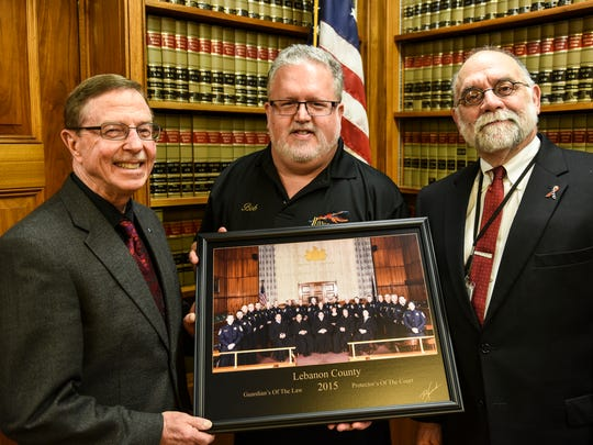 Sheriff Bruce Klingler, from left, photographer Robert Howard and President Judge John Tylwalk pose for a photo after Howard donated a photo of all five Lebanon County judges and all 21 sheriff deputies on Friday, March 4, 2016. This is the first time a picture like this has been taken. The photo was taken on Oct. 19, 2015, and Howard donated his services and the print, which hangs in the judges' chambers.