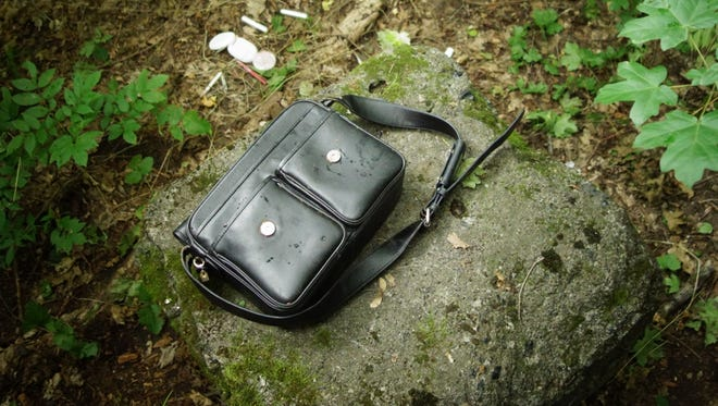 A handbag rests on the ground near the crash site of Malaysia Airlines Flight MH17. It is unclear how many personal items have gone missing, but in the field and forest, evidence of looting is clear.