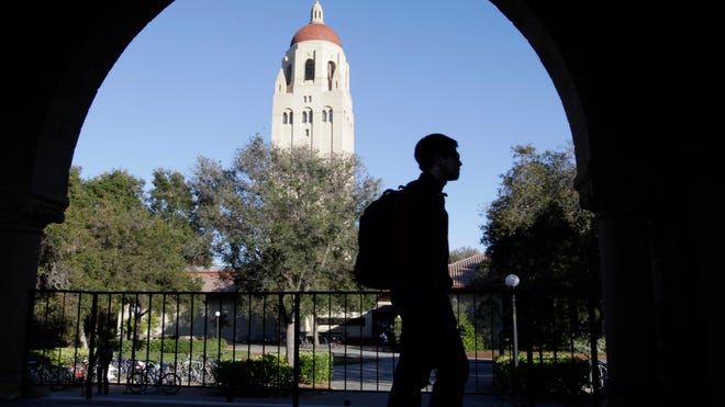 A Stanford University student walks in front of Hoover Tower on the Stanford University campus in Palo Alto, Calif.