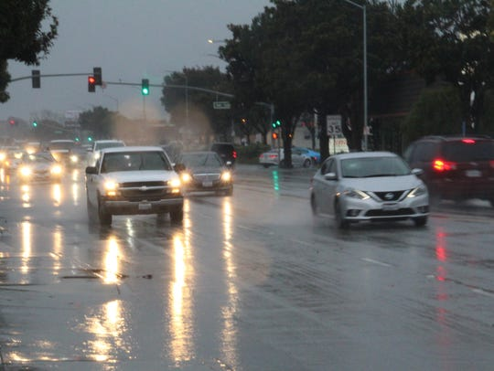 Drivers on S. Main Street Thursday during a rainstorm.