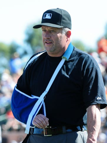 Umpire Dale Scott leaves the game after being hit by