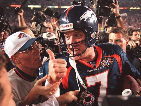 Quarterback John Elway #7 of the Denver Broncos gives