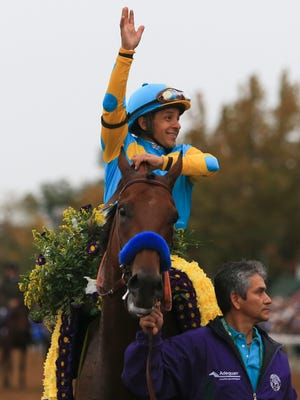 Victor Espinoza waves aboard American Pharaoh after their win the Breeders' Cup Classic Saturday at Keeneland.