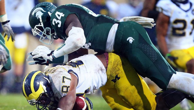 Nov. 2, 2013: Michigan Wolverines tight end Devin Funchess (87) is tackled by Michigan State Spartans linebacker Taiwan Jones (34).
