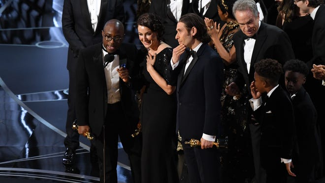 After a two-minute 'La La Land' win for best picture was a mistake, director Barry Jenkins (left) accepts the award for 'Moonlight.'