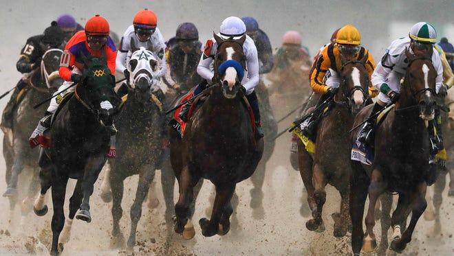 Horses head into the first turn of the Kentucky Derby at Churchill Downs.
