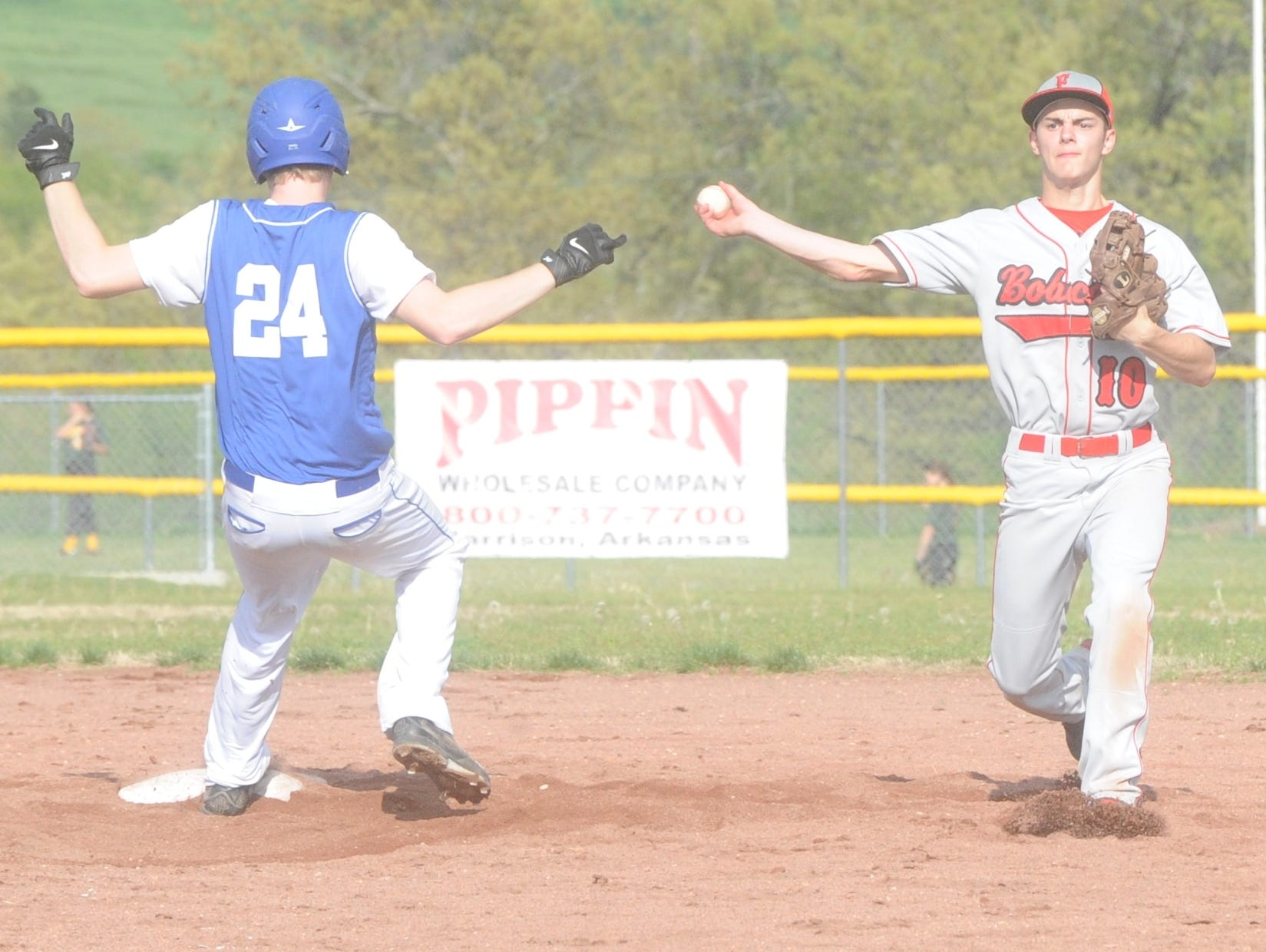 Flippin shortstop Landry Kopacz, right, attempts to turn a double play, while Cotter's Aron Rowe goes into second base during the Bobcats' 2-1 victory over the Warriors on Friday at Warrior Field.