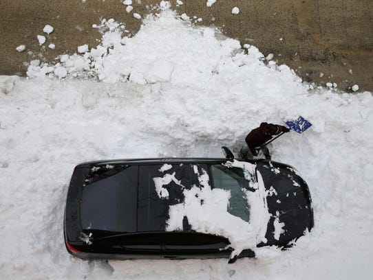 A woman attempts to dig her car out from underneath