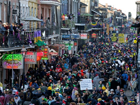 Revelers pack Bourbon Street beneath the balcony of