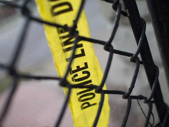 Remnants of crime scene tape remain on a fence in Foster