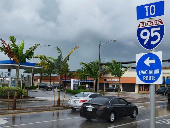 A sign points to an evacuation route as South Florida