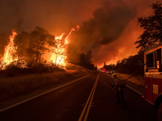 A firefighter battles a wildfire as it threatens to