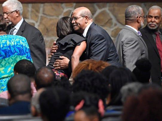 Harry Decour hugs a member after prayers were said