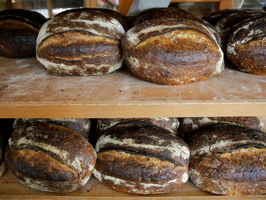 Freshly baked loaves of bread on a rack at the Tartine