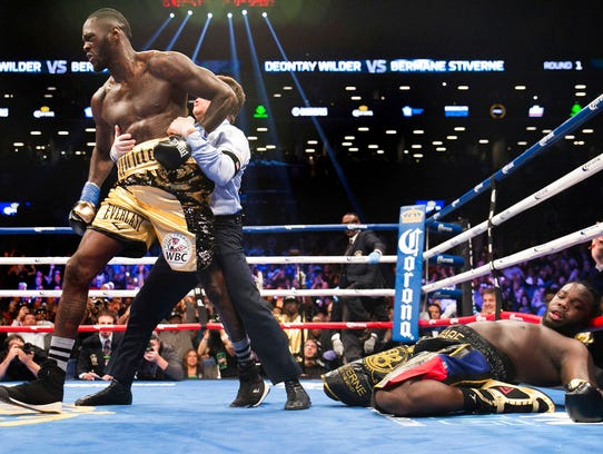 A referee pulls Deontay Wilder away from Bermane Stiverne