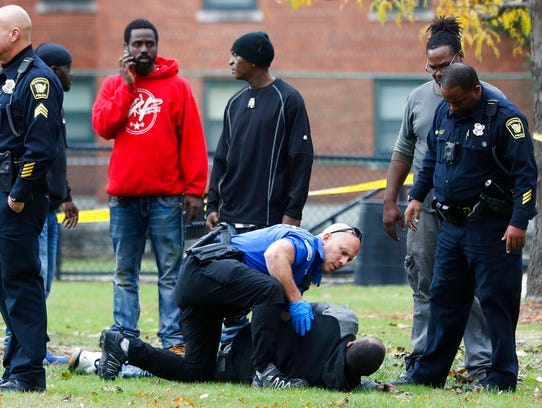 Police respond to a crime scene after a suspect fired multiple rounds into a park and playground, wounding at least one, before feeling the area, Thursday, Nov. 2, in Cincinnati. The suspect was arrested and identified as Isaiah Currie.