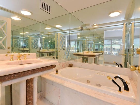 The master bathroom features a mirror wall and full