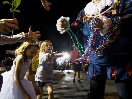 A girl reaches for beads as they are passed out to
