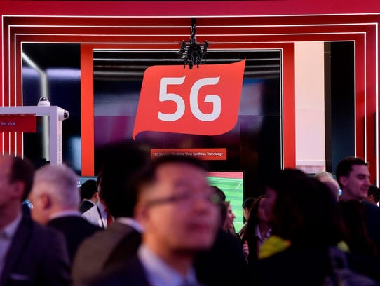 People walk by a 5G stand at the Mobile World Congress