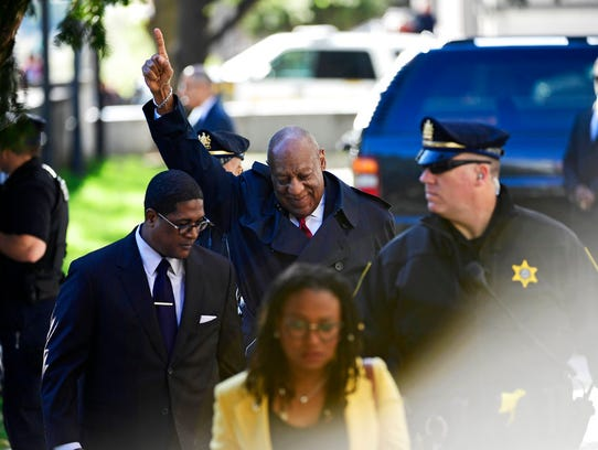 Bill Cosby, center, reacts after spokesperson Andrew