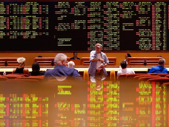 People sit in the sports book at the South Point hotel-casino, Monday, May 14, 2018, in Las Vegas. The Supreme Court on Monday gave its go-ahead for states to allow gambling on sports across the nation.